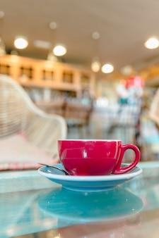 Tazza di caffè rossa sul contatore di vetro nel caf�