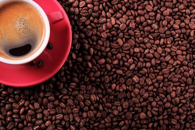 Tazza di caffè rosso con vista dall'alto di chicchi di caffè e tostato