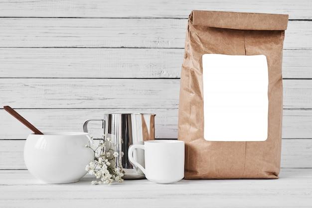 Tazza di caffè, sacchetto di carta artigianale e brocca in acciaio inossidabile