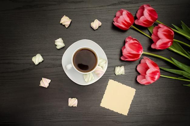 Tazza di caffè, saluti puliti, marshmallow e tulipani rosa. sfondo nero. vista dall'alto