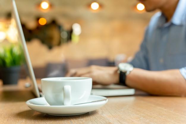 Tazza di caffè selezionata del fuoco con l'uomo d'affari che lavora al computer portatile nella priorità bassa.