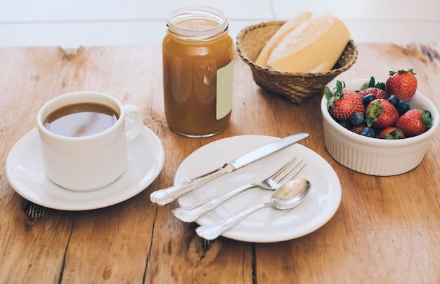 Tazza di caffè; set di posate; barattolo di marmellata; pane e bacche sul tavolo di legno