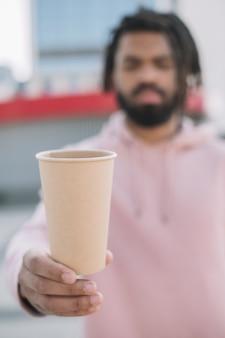 Tazza di caffè sfocato della holding dell'uomo