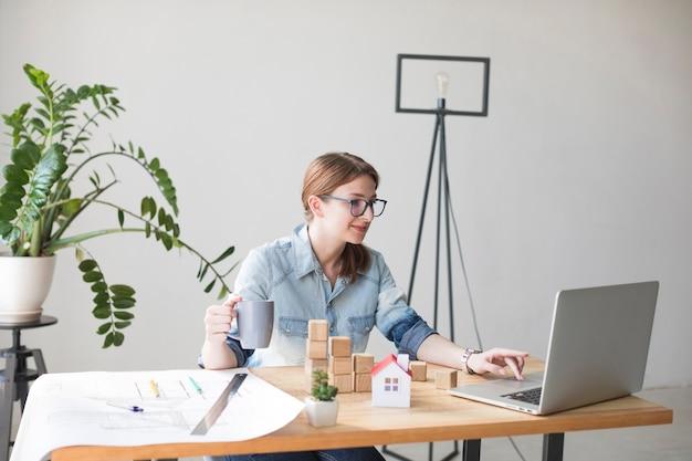 Tazza di caffè sorridente sorridente della tenuta della donna mentre lavorando al computer portatile