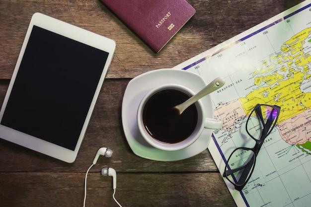 Tazza di caffè su legno rustico con ipad e passaporto e orologio e mappa