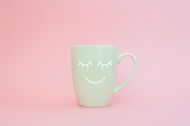 Tazza di caffè su sfondo rosa con volto sorriso felice
