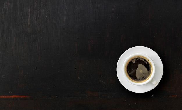 Tazza di caffè su struttura di legno verniciato nero