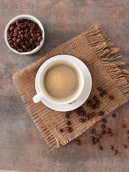 Tazza di caffè su tela di sacco e chicchi di caffè