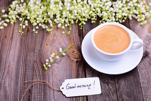 Tazza di caffè su un piattino, accanto a un mazzo di mughetti bianchi