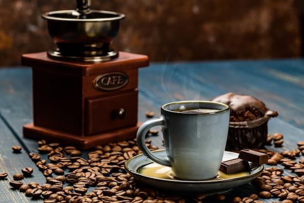 Tazza di caffè su un tavolo di legno blu con chicchi di caffè e un cioccolato