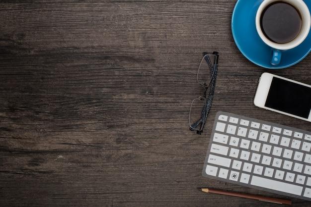 Tazza di caffè su una scrivania con un computer portatile e un paio di occhiali per vedere