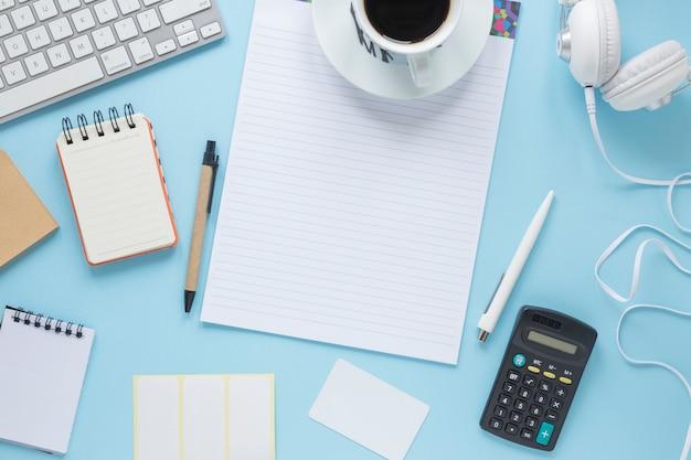 Tazza di caffè su una sola riga; blocco note a spirale; penna; tastiera; cuffia su sfondo blu