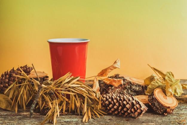 Tazza di caffè su una tavola di legno tra le foglie e coni