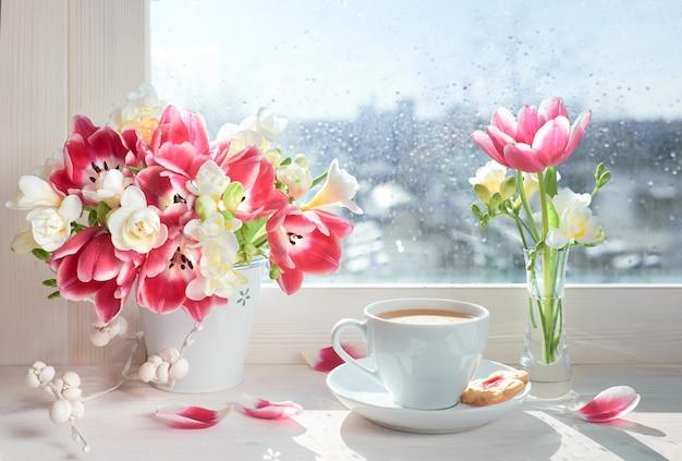 Tazza di caffè sul bordo della finestra, il sole dopo la pioggia con fiori di primavera