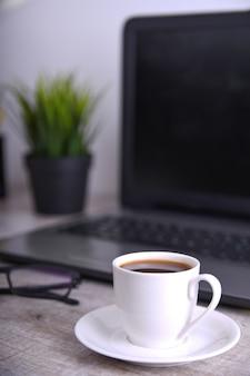 Tazza di caffè sul desktop dell'ufficio con il computer portatile, computer sulla tavola di legno. primo piano, con spazio per il testo