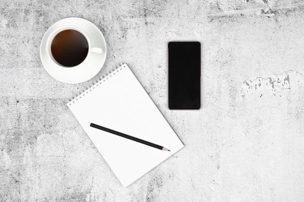 Tazza di caffè sul posto di lavoro. stile piatto laico. sfondo di cemento grigio chiaro.