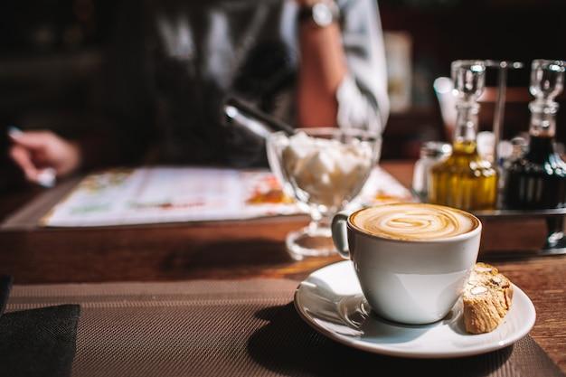 Tazza di caffè sul tavolo in un accogliente bar. menu lettura donna seduto di fronte, volto non visibile. copyspace.