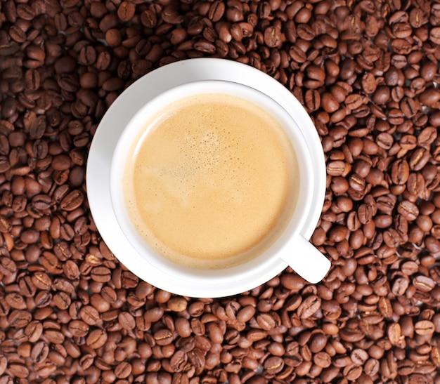Tazza di caffè sulla superficie dei chicchi di caffè