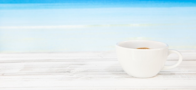 Tazza di caffè sulla tavola di legno bianca con il mare blu luminoso