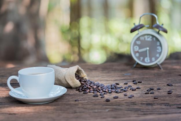 Tazza di caffè sulla tavola di legno con i fagioli e la sveglia sul fondo verde del bokeh della natura.
