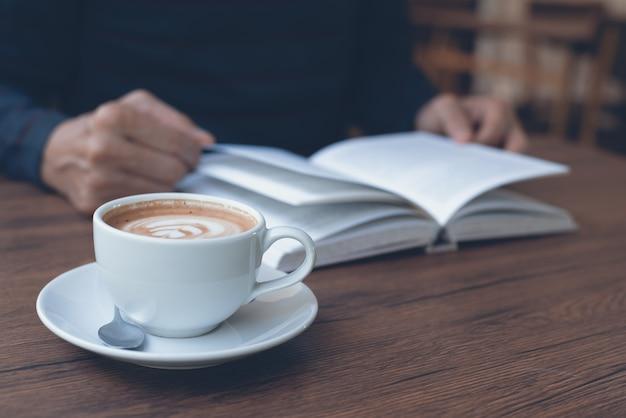 Tazza di caffè sulla tavola di legno con un libro di lettura dell'uomo