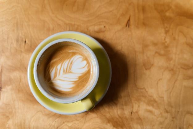Tazza di caffè sulla vista di legno del piano d'appoggio. latte alternativo. sfondo di metà del secolo in legno. schiuma art