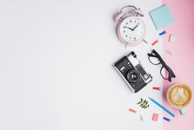 Tazza di caffè; sveglia; macchina fotografica retrò; occhiali da vista e retro macchina fotografica su doppio contesto bianco e rosa