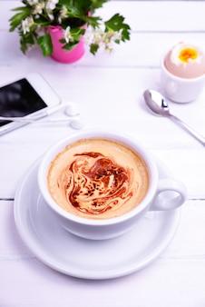 Tazza di caffè, uova e telefono cellulare