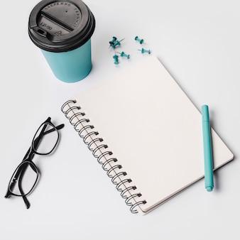 Tazza di caffè usa e getta; penna; occhiali; blocco note a spirale; perni della puntina da disegno su sfondo bianco