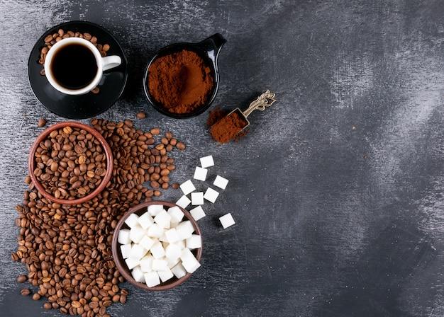 Tazza di caffè vista dall'alto con chicchi di caffè e zollette di zucchero sul tavolo scuro