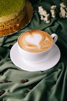 Tazza di cappuccino con chicchi di caffè e torta sul tavolo