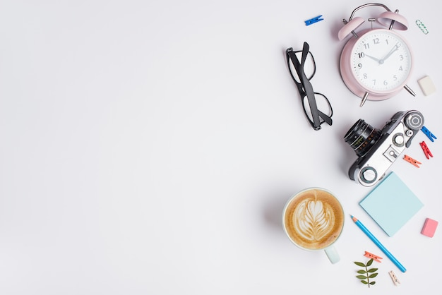 Tazza di cappuccino con latte art; macchina fotografica d'epoca; sveglia; matita e occhiali su sfondo bianco