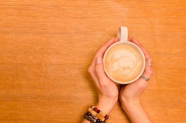 Tazza di cappuccino in mani femminili. tavolo in legno, copia spazio. vista dall'alto