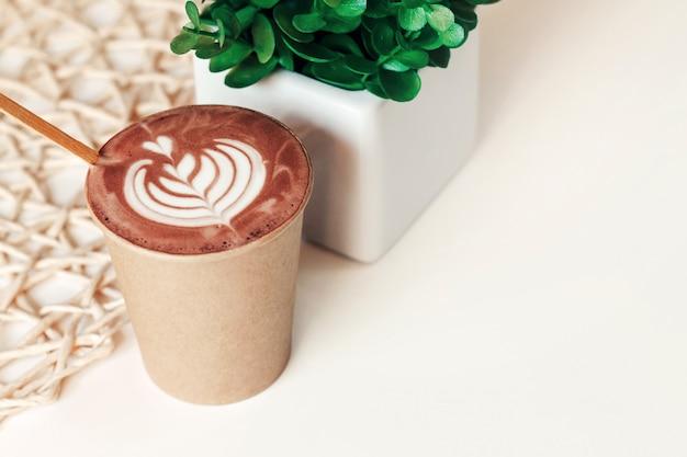 Tazza di cappuccino in una tazza di carta con un modello su un tavolo in un caffè, copia spazio