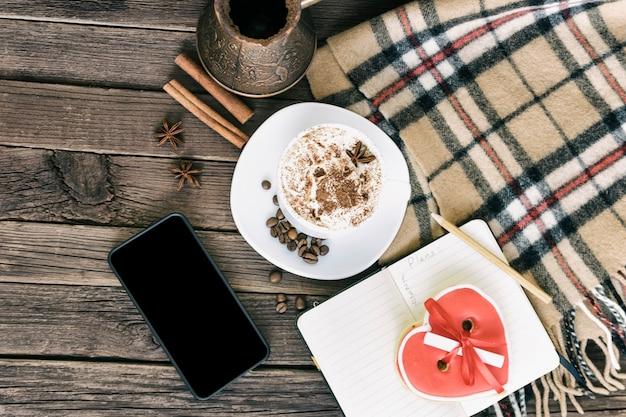 Tazza di cappuccino, messaggio di larghezza dei biscotti a forma di cuore, smartphone e caffettiere su una tavola di legno marrone