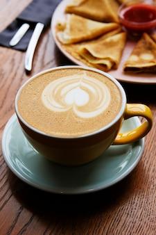 Tazza di cappuccino nel caffè. accanto a un piatto di pancake e marmellata di lamponi. pausa caffè.