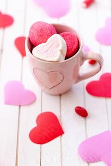 Tazza di caramelle gommosa e molle a forma di cuore e cuore