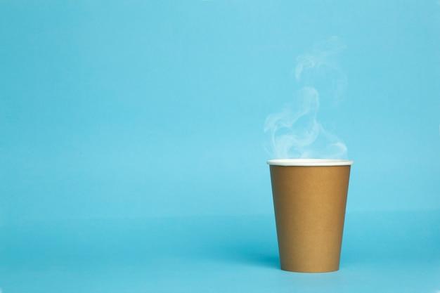 Tazza di carta con caffè caldo su sfondo blu.