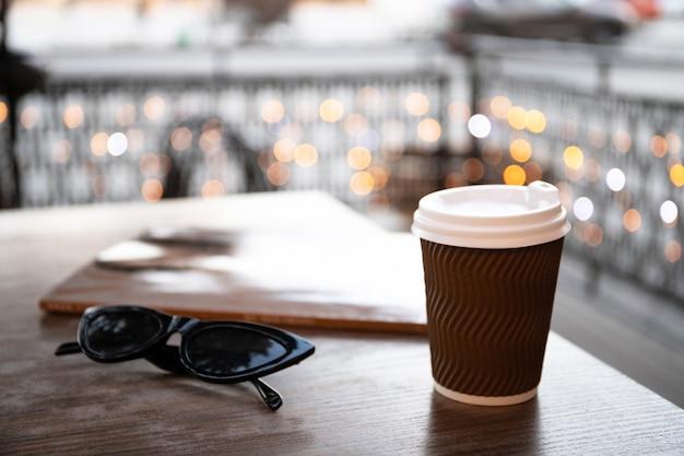 Tazza di carta con caffè e una rivista su un tavolo