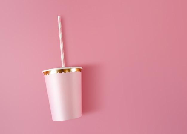 Tazza di carta con cannucce su sfondo rosa