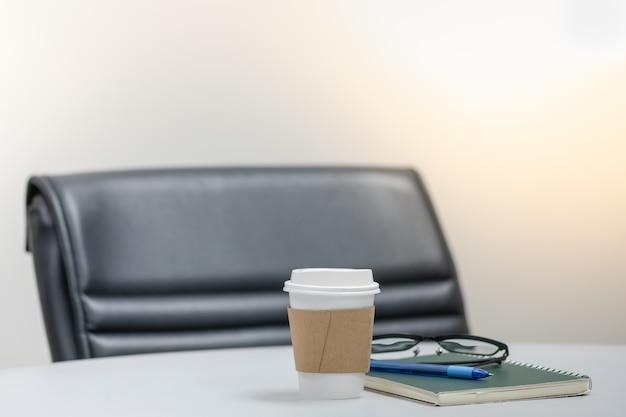 Tazza di carta di caffè caldo sulla tavola bianca con il taccuino, la penna, i vetri di lettura e la poltrona nera nella sala riunioni.