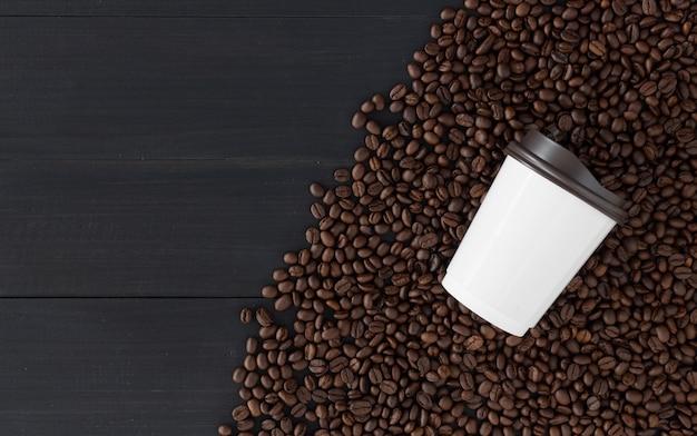 Tazza di carta e chicco di caffè su fondo di legno nero. vista dall'alto