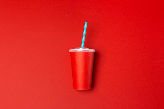 Tazza di carta rossa isolata sul rosso,