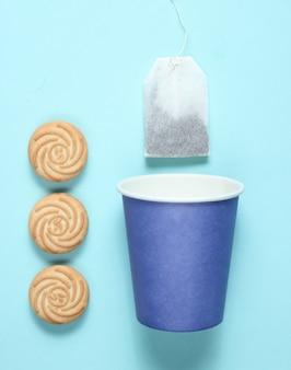 Tazza di carta usa e getta vuota per tè, bustina di tè, biscotti sulla superficie blu pastello, vista dall'alto, minimalismo