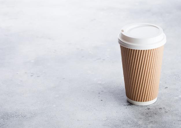 Tazza di cartone per caffè da asporto o caffè per andare su cucina in pietra. colore marrone.