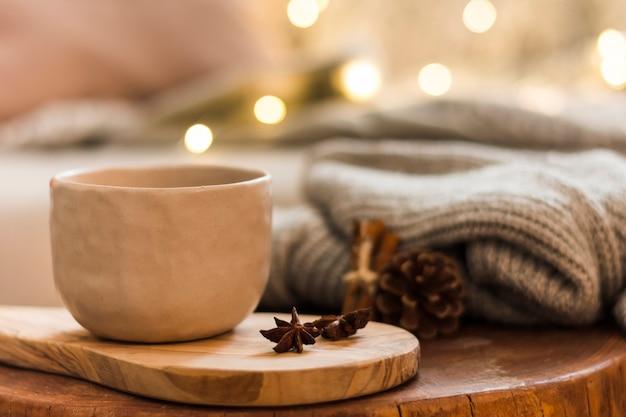Tazza di ceramica decorativa sul cuscinetto caldo di legno