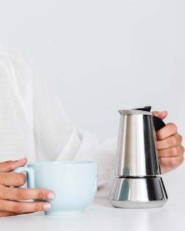 Tazza di ceramica e bollitore da caffè del primo piano