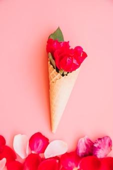 Tazza di cialda con fioritura vinosa vicino al mucchio di petali