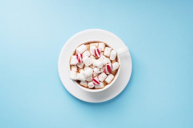 Tazza di cioccolata calda con cacao in polvere e caramello della caramella gommosa e molle su fondo blu pastello con lo spazio della copia. concetto di natale inverno.