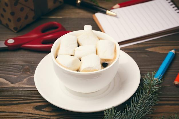 Tazza di cioccolata calda con caramelle gommosa e molle su fondo di legno